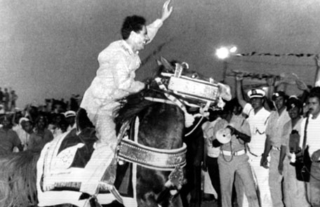 Gaddafi waves to a crowd as he rides a horse during a ceremony marking the sixth anniversary of the eviction of Italians from Libya. 1976(AP)